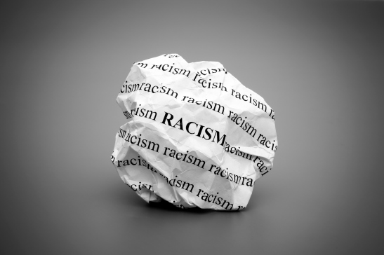 Crumpled paper ball with words Racism on gray background